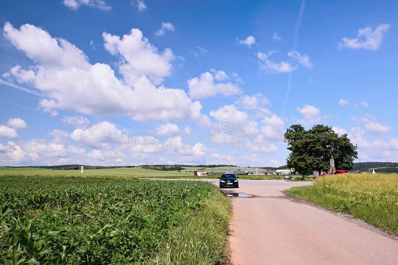Veverske Kninice, Czech republic - June 02, 2018: Spring moravian landscape with path between flowering fields with black car Opel. Astra in foreground and royalty free stock photography