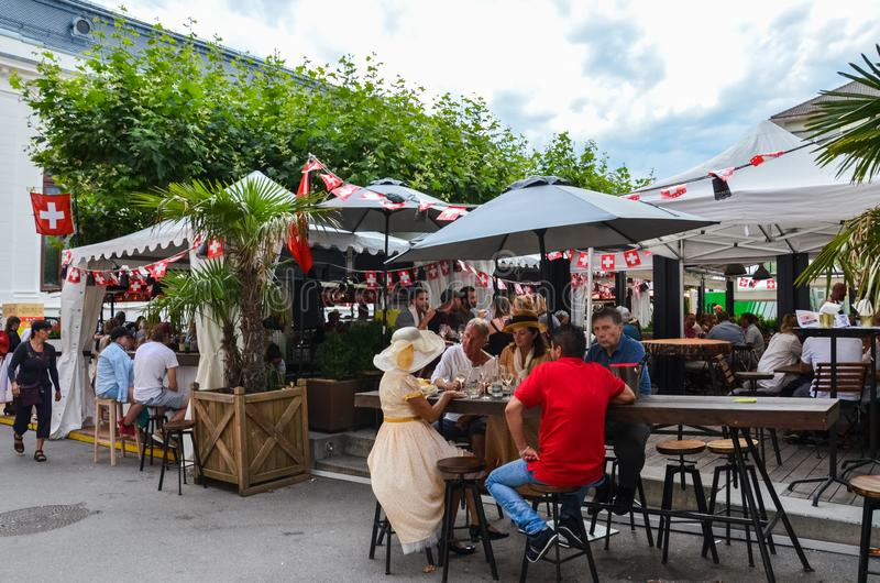 Vevey, Switzerland - Aug 1 2019: People celebrating Swiss National Day in outdoor restaurant. Celebration of the founding of the royalty free stock image
