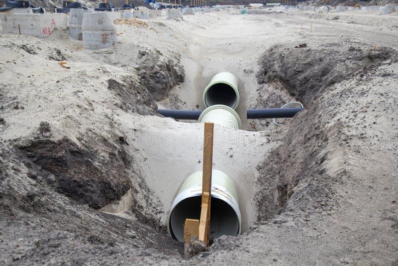 Vezel versterkte die drainagepijpen in het zand worden begraven stock fotografie
