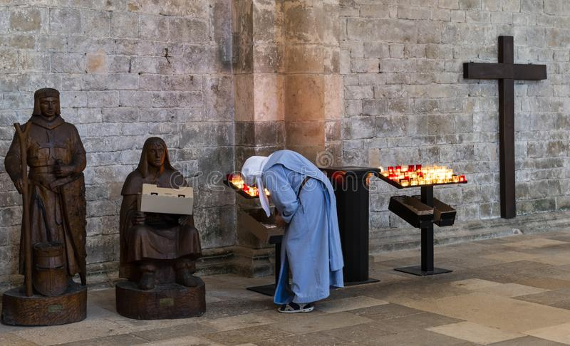 Nun in Church of Vezelay. Vezelay, France - July 29, 2018: Church Interior with nun rearranging the candles of the romanesque abbey and church of Vezelay in royalty free stock photos