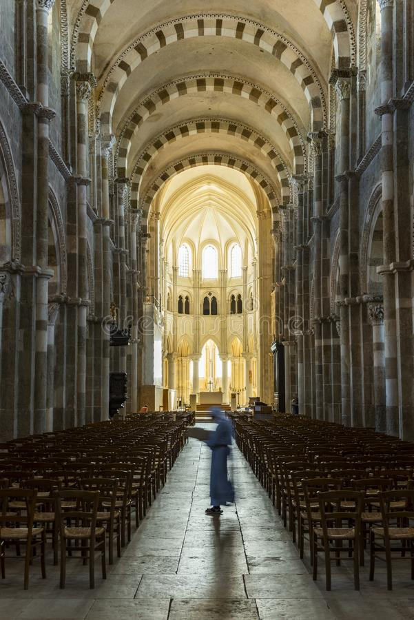 Church in Vezelay with Nun. Vezelay, France - July 29, 2018: Church Interior with nun walking in the romanesque abbey and church of Vezelay in Yonne, France stock photography
