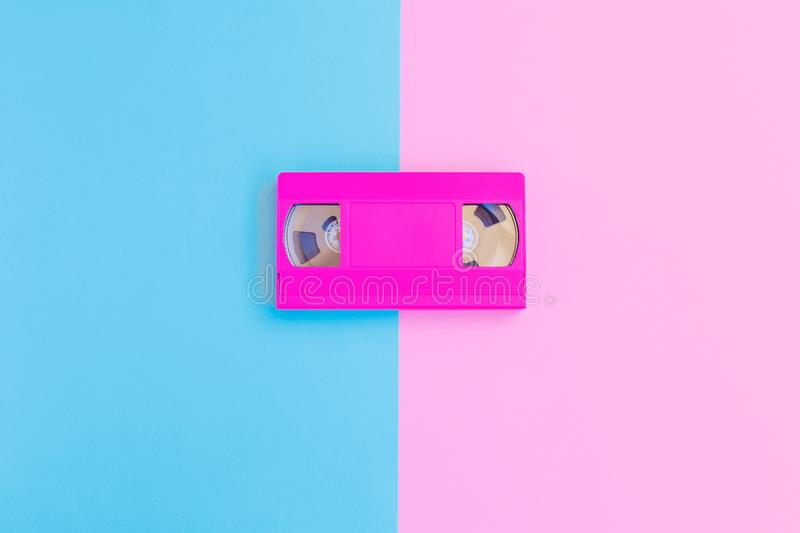 VHS cassette on soft pink and blue paper background. Minimal concept. Creative concept. Cinema concept. stock photos