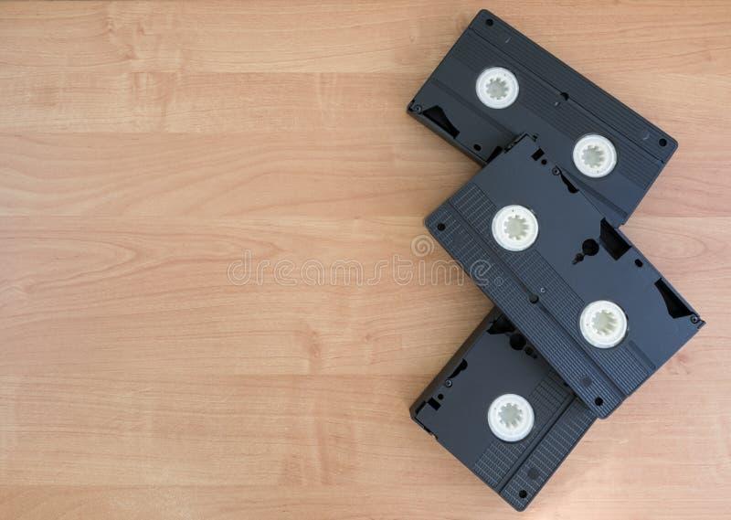 2 VHS noir avec les cuillères blanches se trouvant sur un fond en bois beige images stock