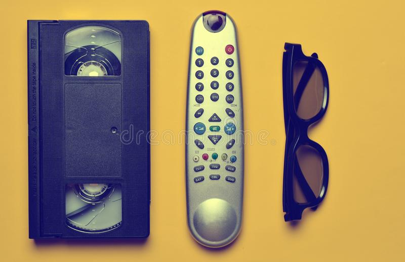 Vhs, TV remote, 3d glasses on a yellow paper background. Entertainment 90s. Top view. Flat lay stock photos