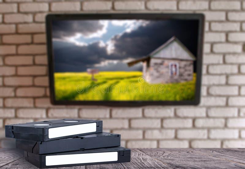 VHS-Videobänder auf der Schreibtischbacksteinmauer mit einem Fernsehen stockbilder