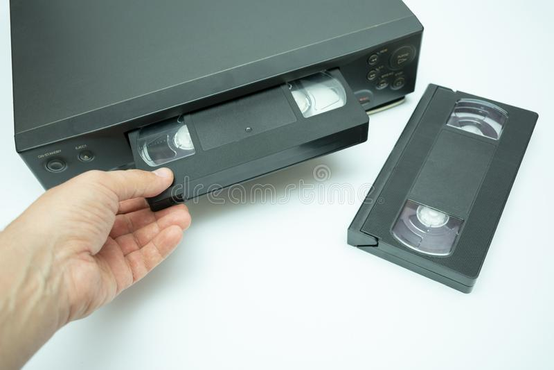 VHS videokassetten sätts in i videoregistreringsapparaten för att hålla ögonen på videoen, en annan videokassett royaltyfria foton