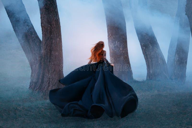 A viúva negra em um vestido de seda escuro longo do laço, uma menina com cabelo vermelho leve lindo foge em uma floresta secreta, imagens de stock royalty free