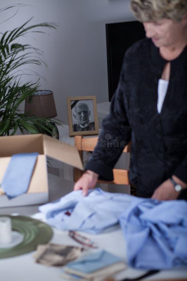 Viúva que embala a roupa do marido inoperante fotografia de stock royalty free