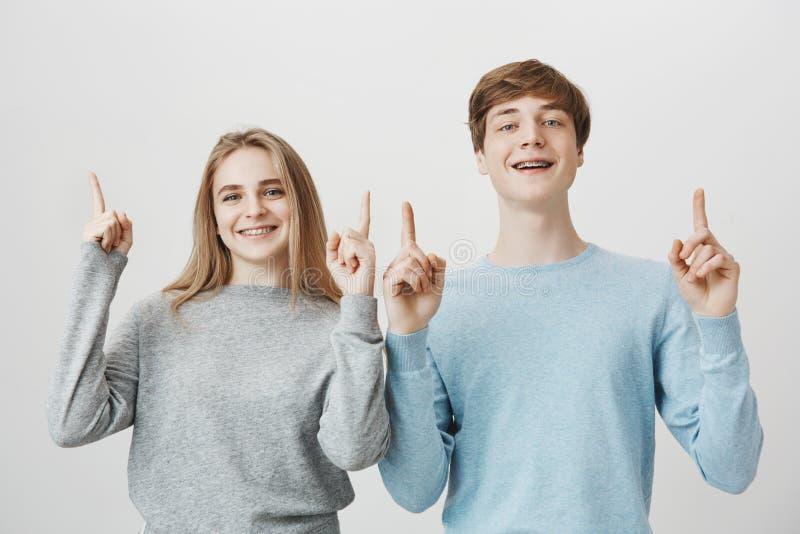 Vi är bästa i allt tillsammans Stående av den säkra vänliga attraktiva mannen och kvinnan som lyfter pekfingrar och royaltyfri bild