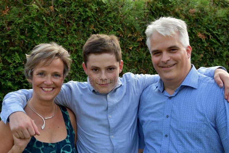 Vi är en lycklig familj, en fadermoder och en tonårs- son royaltyfria bilder
