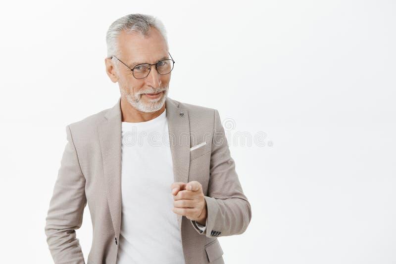 Vi behöver dig mannen Stående av den lyckliga roade och knepiga mogna macho affärsmannen i exponeringsglas och dräkten som ler at arkivbilder