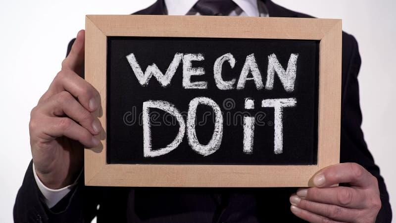 Vi kan göra det motivationuttrycket på svart tavla i affärsmanhänder, service royaltyfria foton