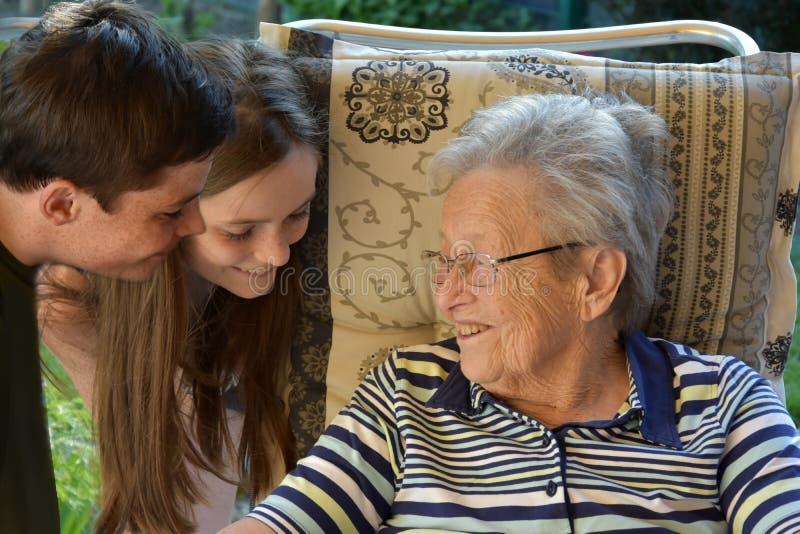 Vi och mormodern, syskon förvånar deras stor-mormor royaltyfri fotografi