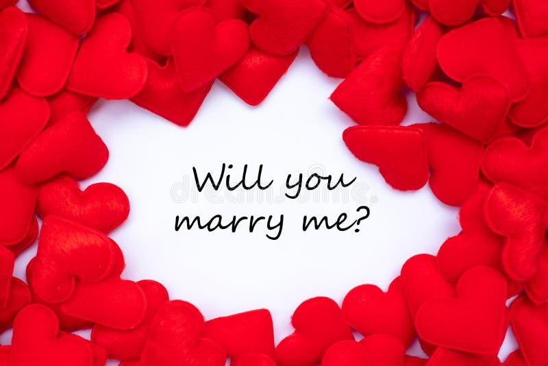 VI SKA ATT GIFTA SIG MIG? ord med röd bakgrund för hjärtaformgarnering För bröllop, romantisk och lycklig Valentine' s dagferie royaltyfri fotografi