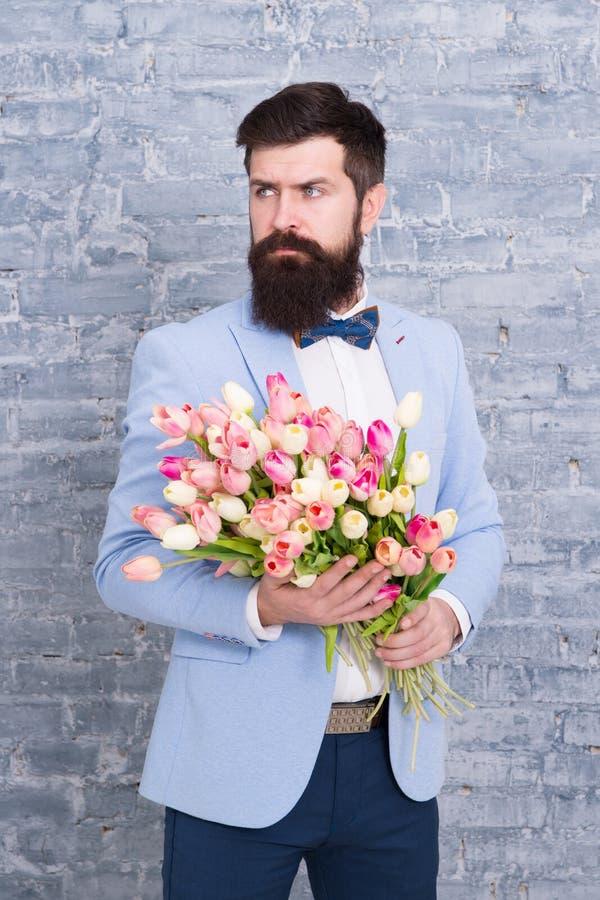 Vi tar blommor personligen Vårgåva Skäggig manhipster med blommor Förälskelse Internationell ferie kvinnors dag royaltyfri foto