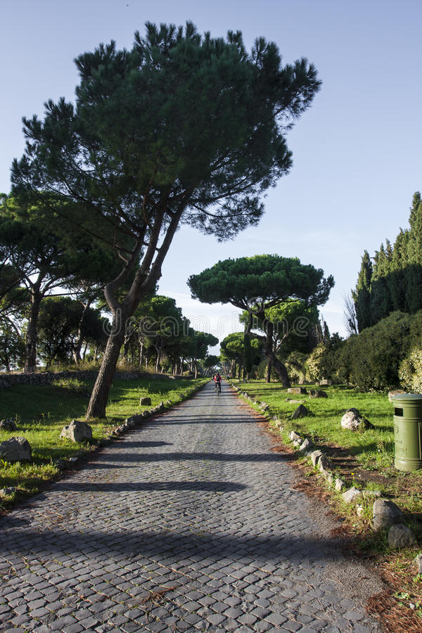 Via Appia Antica, old road build by ancient Romans. The beautiful road path Via Appia Antica in Rome, Italy. Historical road with a lot of Romans ruins royalty free stock image