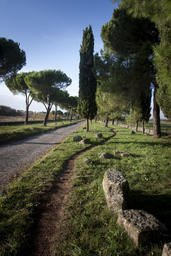Via Appia Antica, old road build by ancient Romans. The beautiful road path Via Appia Antica in Rome, Italy. Historical road with a lot of Romans ruins stock photos