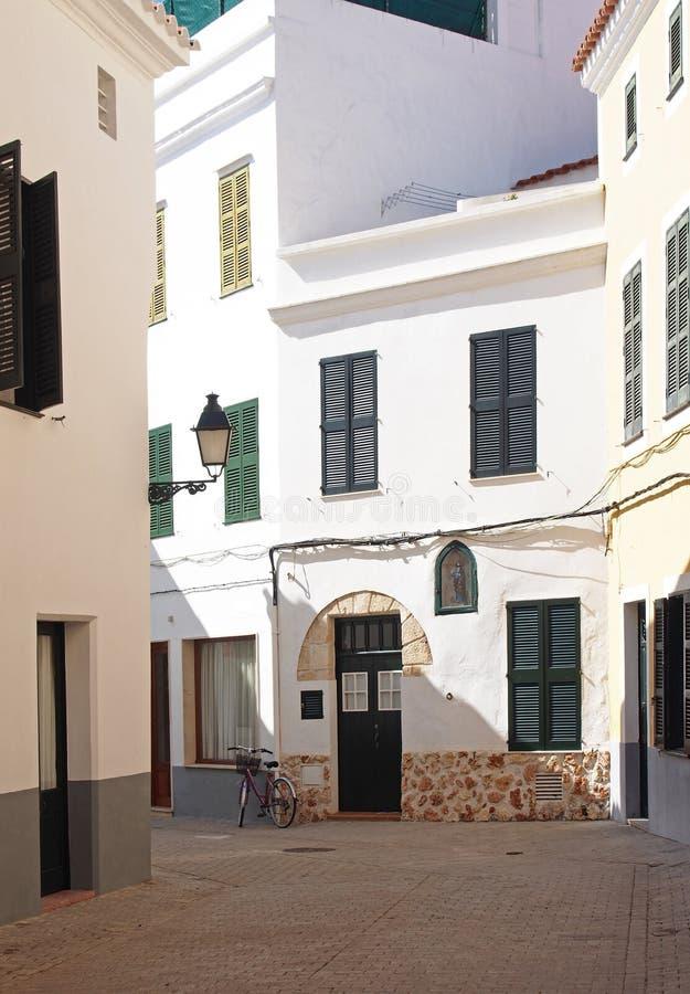 Via cobbled vuota calma con le case tipiche dipinte bianche alla luce solare luminosa di estate con una bicicletta fuori di vecch immagini stock libere da diritti