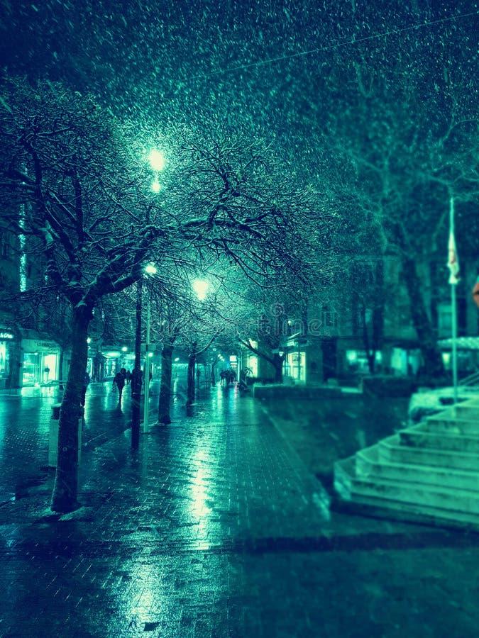 Via della città alla notte nevosa di inverno con la camminata della gente Indicatori luminosi vaghi della città snowfall immagini stock
