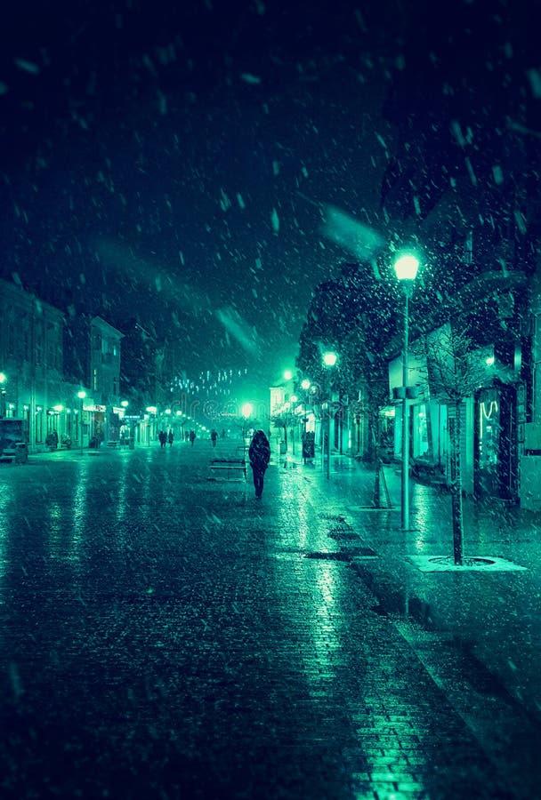 Via della città alla notte nevosa di inverno con la camminata della gente Indicatori luminosi vaghi della città snowfall fotografie stock