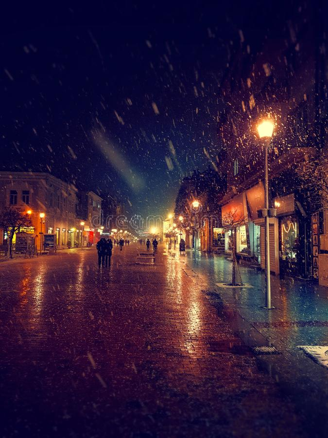Via della città alla notte nevosa di inverno con la camminata della gente Indicatori luminosi vaghi della città snowfall immagine stock