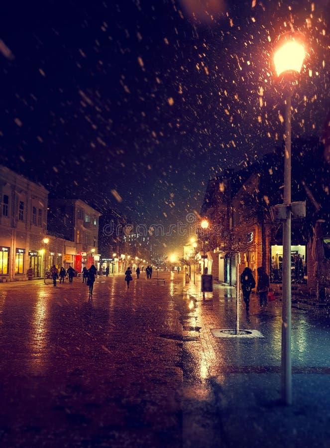 Via della città alla notte nevosa di inverno con la camminata della gente Indicatori luminosi vaghi della città snowfall fotografia stock