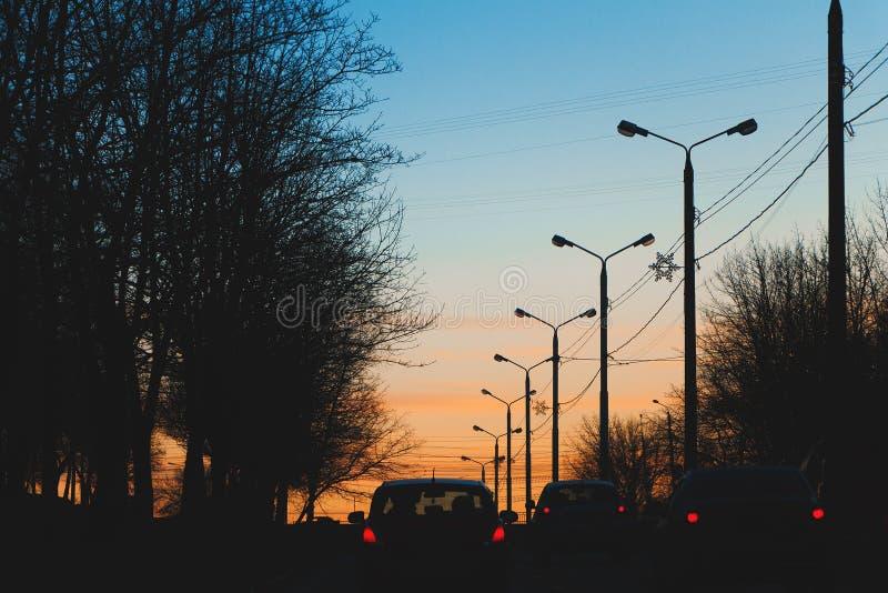 Via della città con i pali della luce nei precedenti del tramonto romantico immagini stock libere da diritti