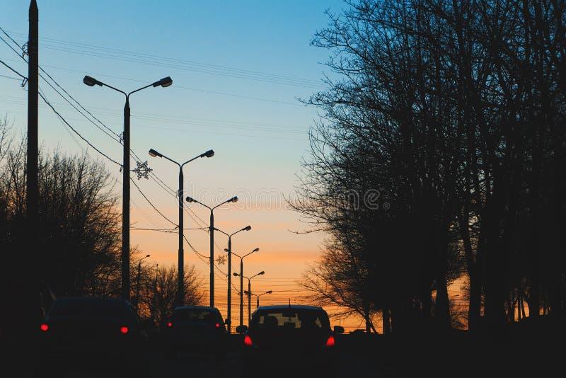 Via della città con i pali della luce nei precedenti del tramonto romantico fotografia stock