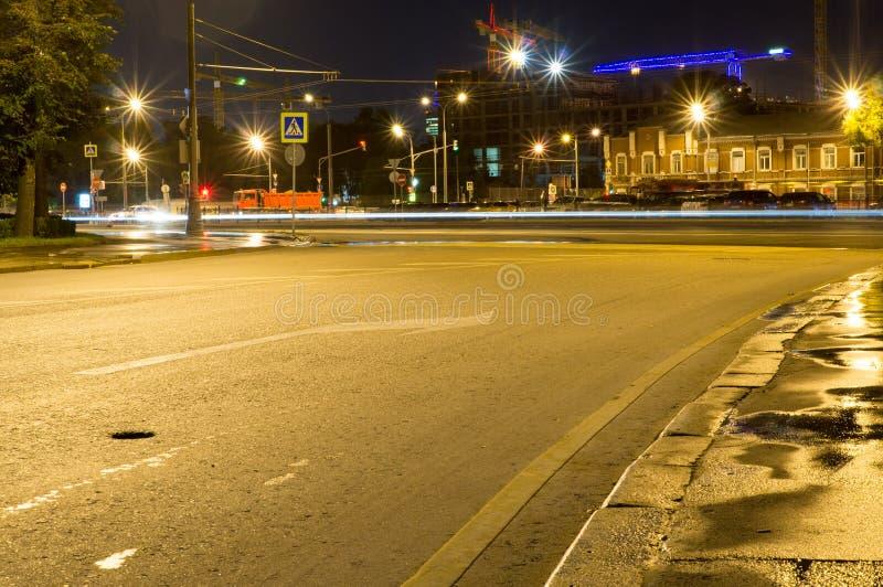 Via della città con le luci ed il traffico alla notte fondo, vita di città fotografia stock