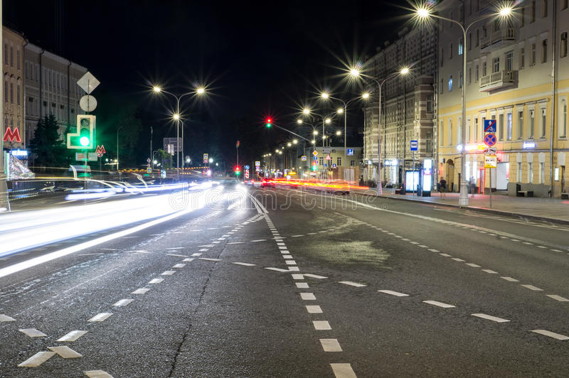 Via della città con le luci ed il traffico alla notte fondo, vita di città immagini stock