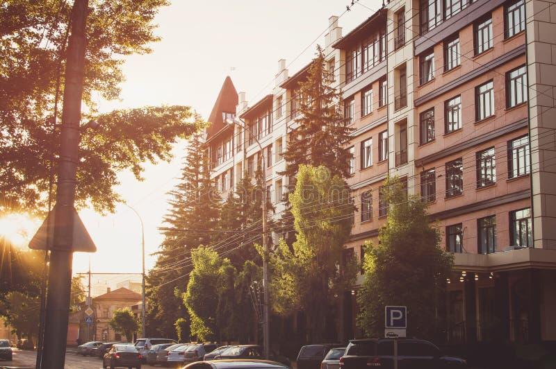 Via della città, delle case e delle automobili alla luce del tramonto fotografie stock libere da diritti