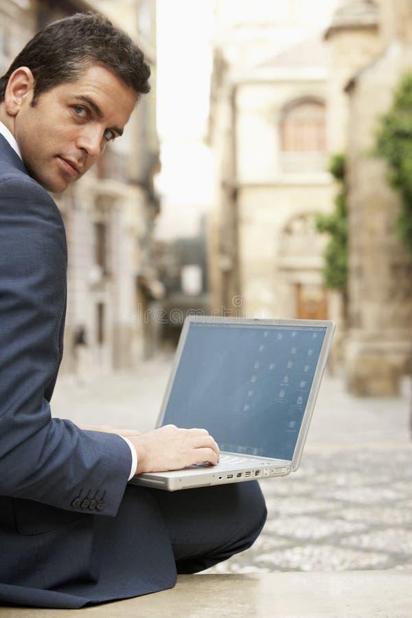 Via della città di Using Laptop On dell'uomo d'affari fotografie stock