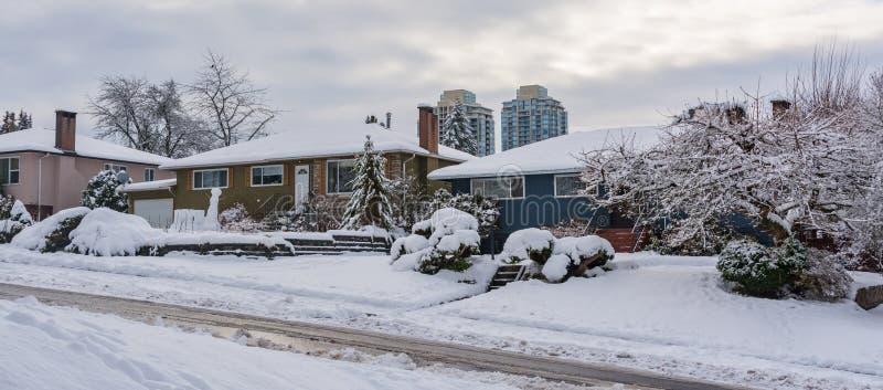 Via delle case residenziali in suburbano Case della famiglia in neve sulla stagione invernale immagine stock libera da diritti