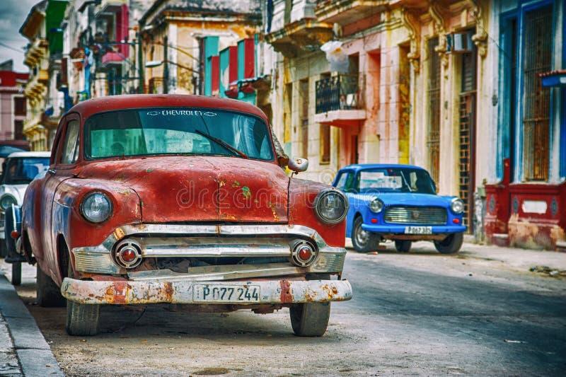 Via di Avana in Cuba con la vecchia automobile americana rossa fotografie stock libere da diritti
