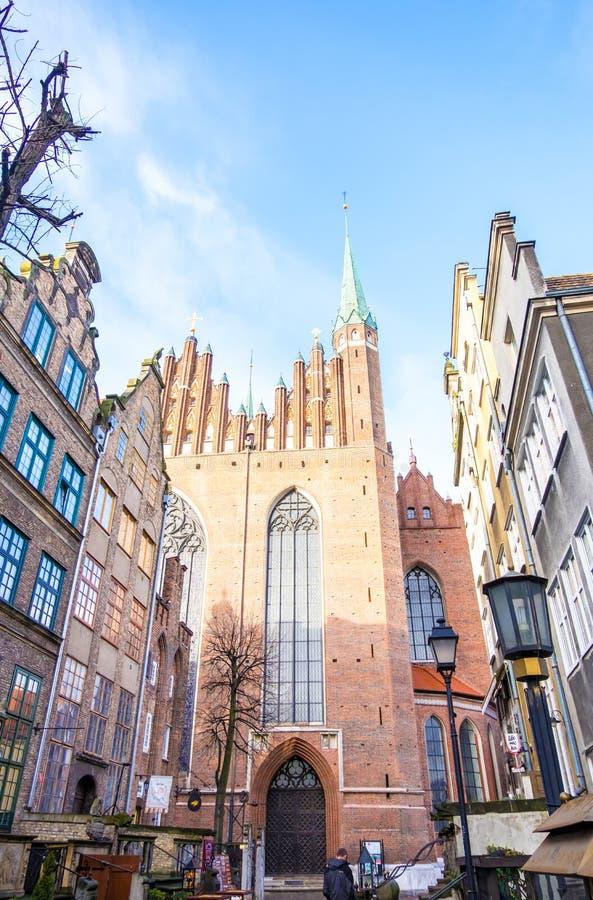 Via di Mariacka con le facciate variopinte delle case in affitto e della chiesa gotica del XVI secolo del ` s di St Mary, Danzica fotografia stock libera da diritti