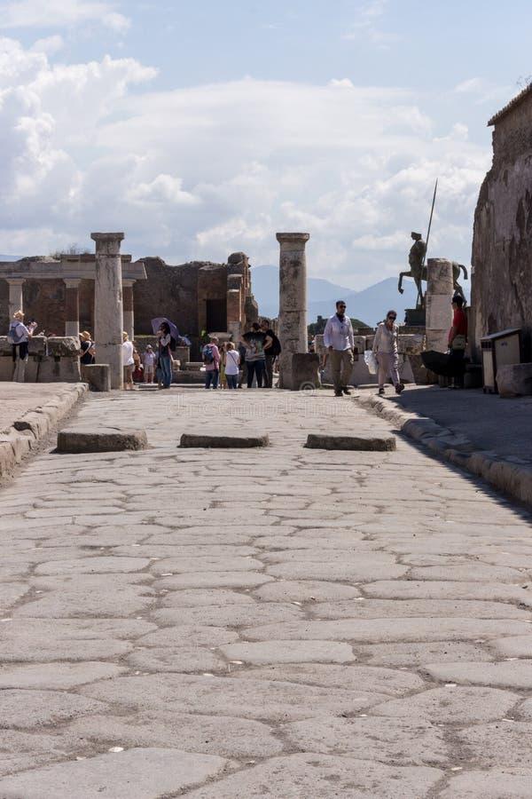 Via di pietra antica con le colonne e statua e turisti a Pompei, Italia Concetto antico della cultura Rovine di Pompei immagine stock
