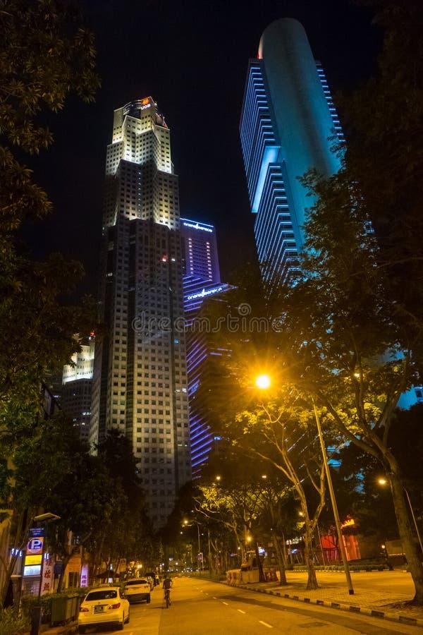 Via ed alte costruzioni del grattacielo contro il cielo a Singapore alla notte immagini stock