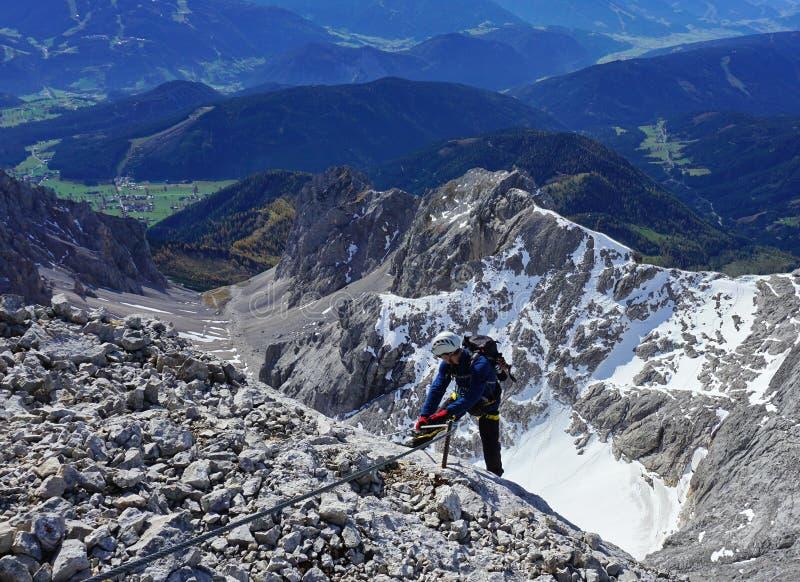 Via ferrata climber on a rock top view stock photography