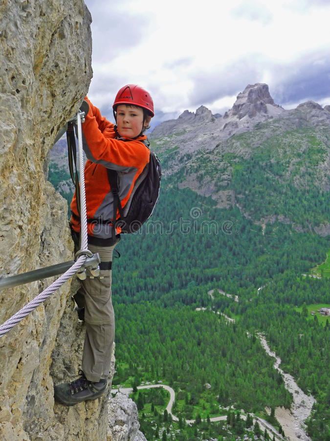 Via Ferrata with young boy. A boy climbing a 'Via Ferrata' in the Italian Dolomites stock images
