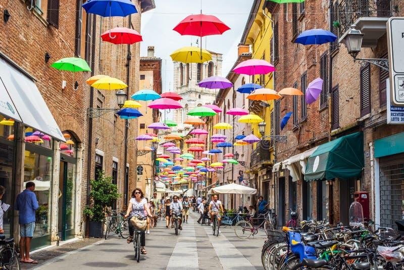 Via Giuseppe Mazzini of Ferrara. Emilia-Romagna. Italy. Ferrara, Italy - July 21, 2016. Cyclists crossing Via Giuseppe Mazzini of Ferrara covered with colored royalty free stock photo