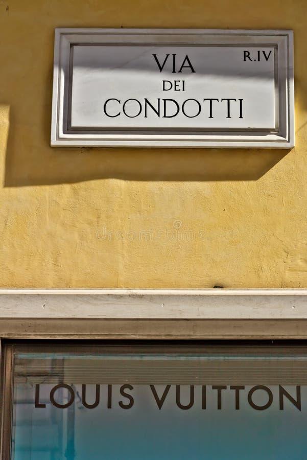 Via il segnale stradale di Dei Condotti a Roma Segno inferiore del boutique di Louis Vuitton fotografie stock