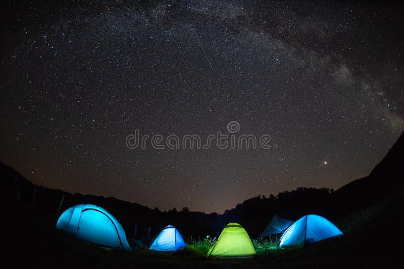 A Via Látea com as barracas que iluminam na noite, montanhas aventura-se no chuveiro de meteoro de Perseid foto de stock