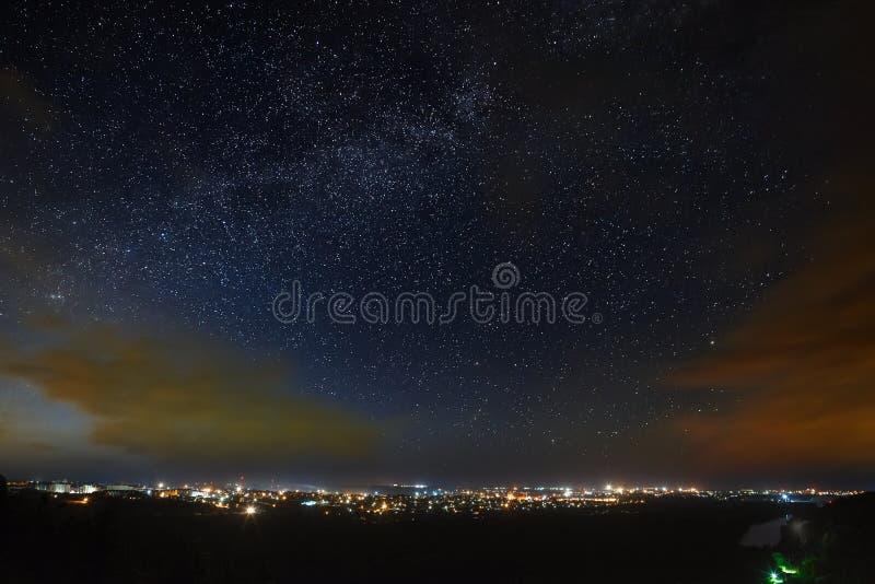 A Via Látea do céu noturno estrelado acima da cidade fotos de stock royalty free