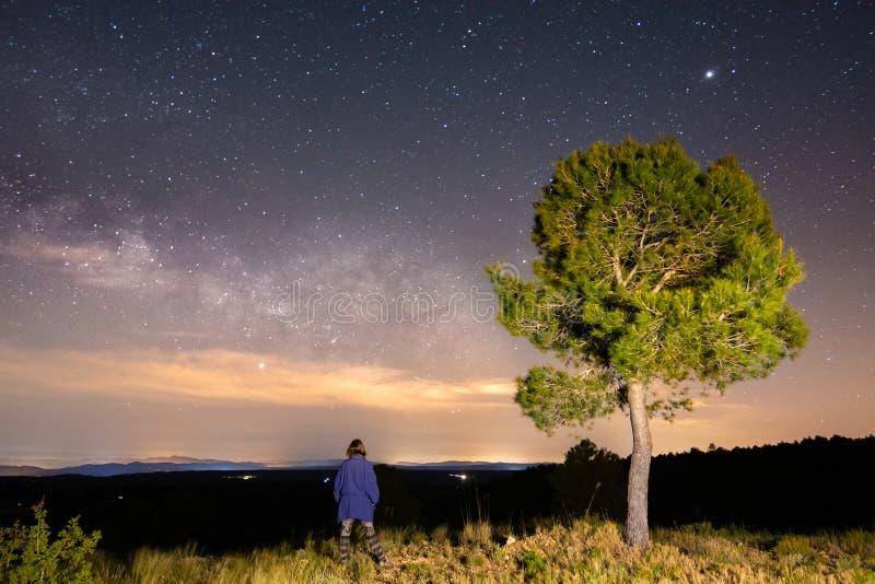 Via Lattea con una ragazza accanto all'albero sulla collina Via Lattea con i viaggiatori Universo immagini stock libere da diritti