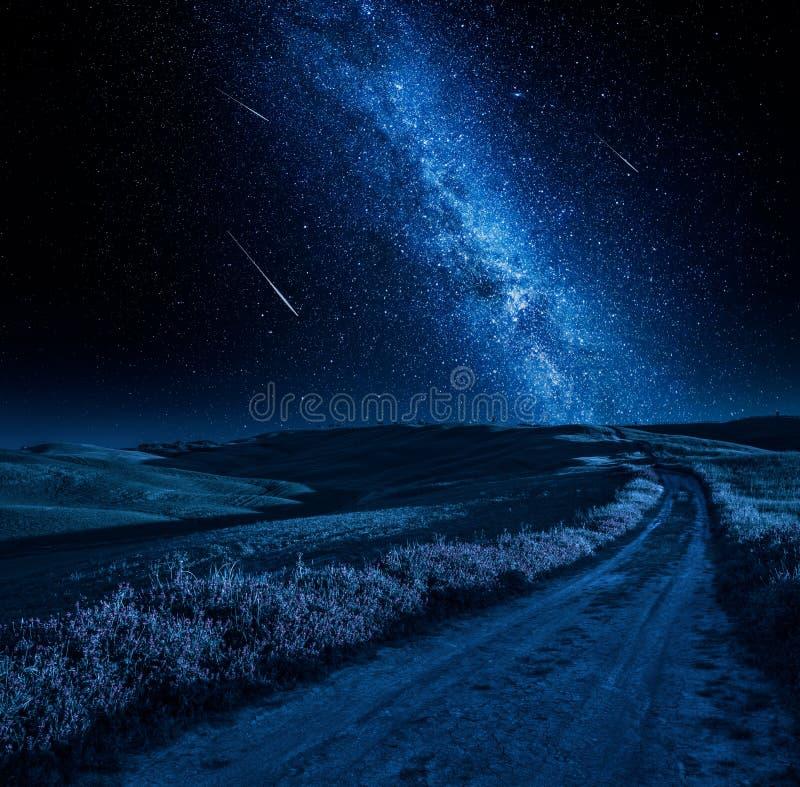 Via Lattea di stordimento sopra la strada campestre alla notte fotografia stock