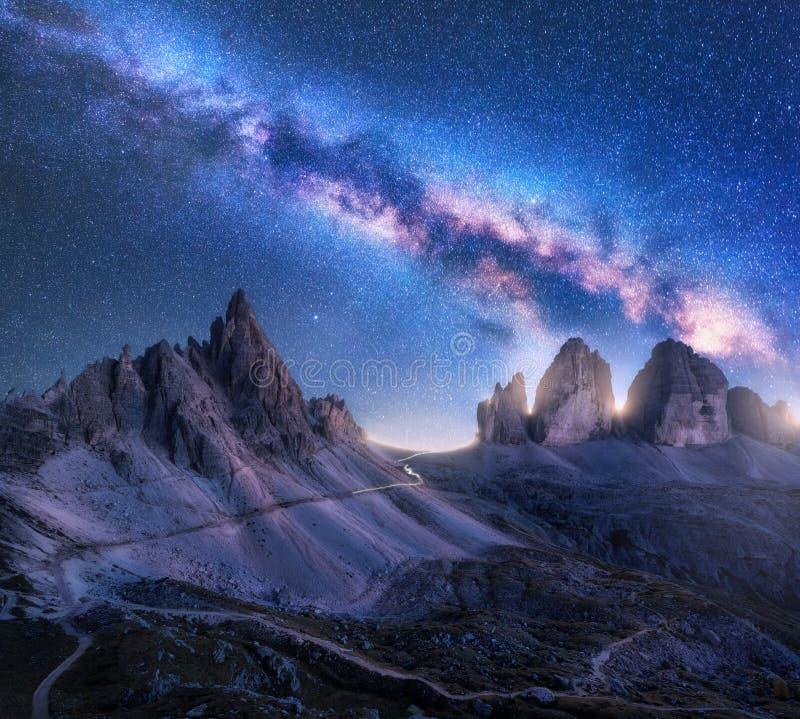 Via Lattea luminosa sopra le montagne alla notte stellata nell'estate fotografia stock