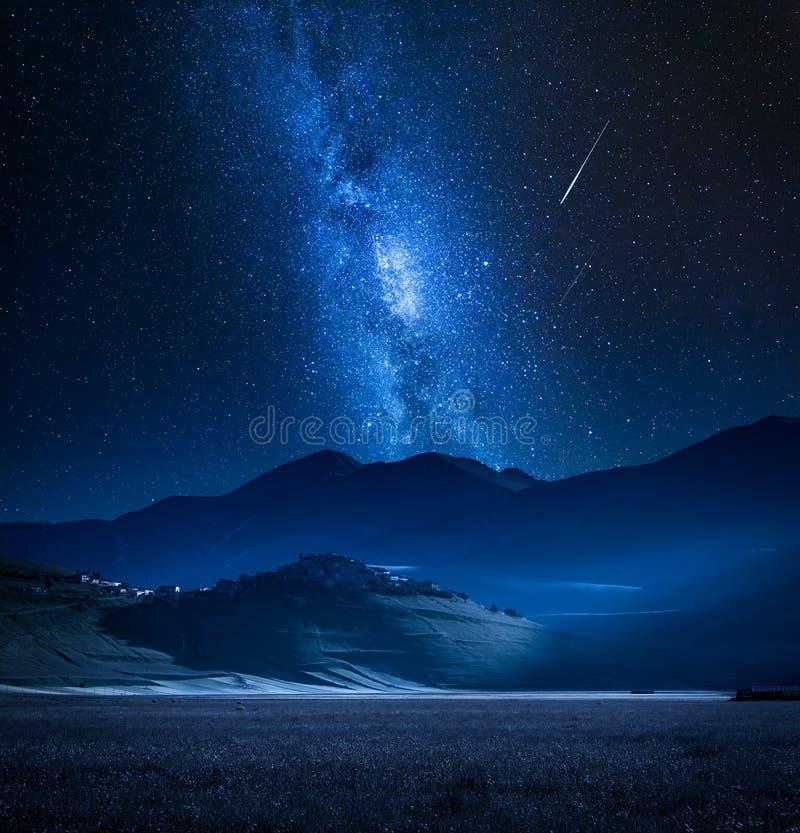 Via Lattea meravigliosa sopra Castelluccio alla notte, Umbria, Italia fotografia stock