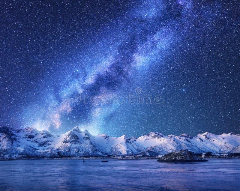 Via Lattea porpora sopra le montagne innevate e mare alla notte fotografia stock libera da diritti
