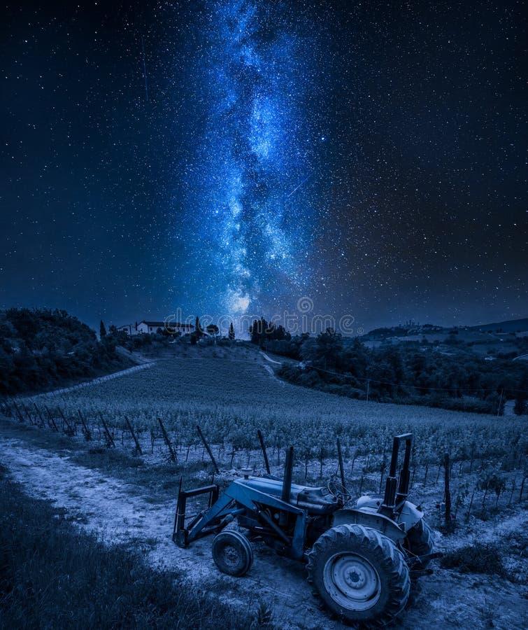 Via Lattea sopra le viti ed il vecchio trattore un la notte, Toscana fotografia stock libera da diritti