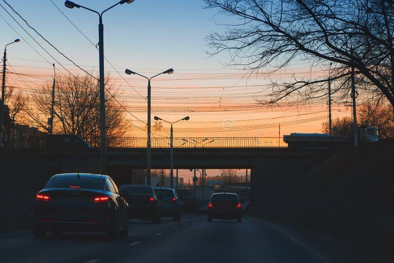 Via, ponte, automobili e pali della luce urbani sui precedenti del tramonto romantico fotografia stock libera da diritti